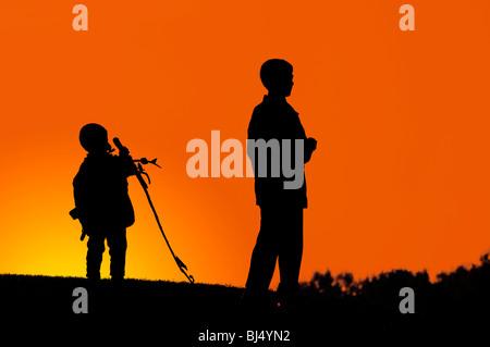 Zwei jungen stehen auf einem Hügel dunkle Silhouette über bunte Digital angepasst orange Abendhimmel - Stockfoto