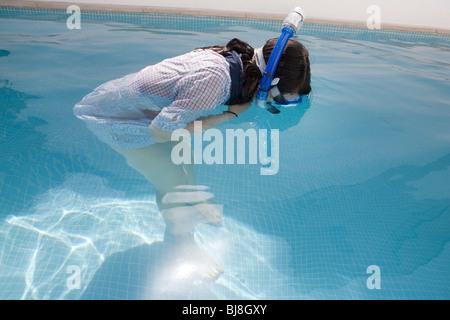 Mädchen mit Kleidern und Schnorchel Studium Ende Schwimmbad - Stockfoto