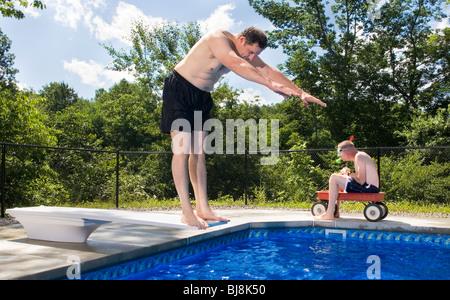Mann bereitet Schwimmbad eintauchen, während sein Freund in einem Radio Flyer roten Wagen tragen eine Tauchermaske - Stockfoto