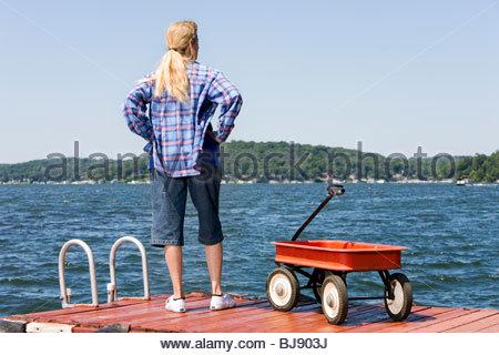Frau stehend auf einem Bootssteg und Blick auf einen See mit einem Radio Flyer roten Wagen neben ihr. - Stockfoto
