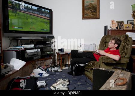 Jungen spielen Videospiel in unübersichtlichen Wohnzimmer - Stockfoto