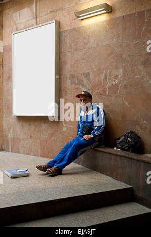 Senior woman Vermietung Schuppen auf Marmortreppe mit leeren Plakatwand im Hintergrund - Stockfoto