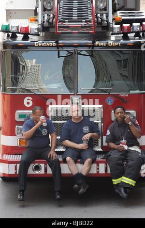 Drei Feuerwehrleute auf ein Feuerwehrauto Bumper sitzen und trinken aus Pappbechern, Chicago, Vereinigte Staaten - Stockfoto