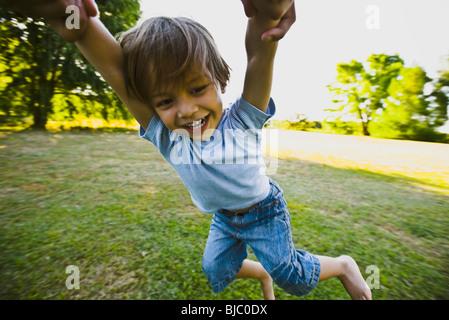 Eltern, die kleinen Jungen im Park, beschnitten die Spinnerei - Stockfoto