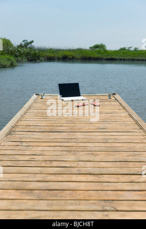 Laptop-Computer und Flip-flops links dock im - Stockfoto