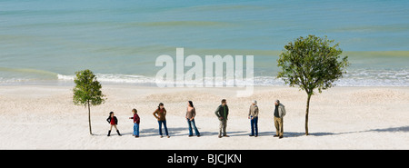 Gruppe von Menschen stehen in Zeile im Chat zwischen zwei Bäumen am Strand - Stockfoto