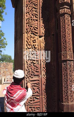 Muslimische Jungen beobachten Islamische Ornamentik des Quran Inschrift auf Qutab Minar geschnitzt; Indo-islamischen - Stockfoto