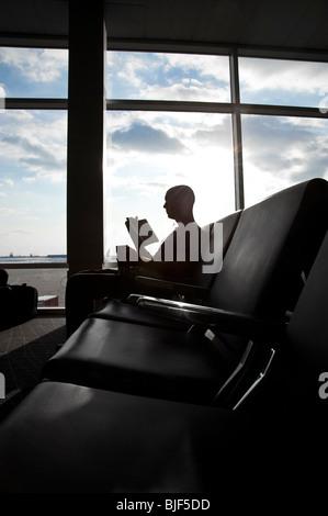 Mann In der Flughafen-Lounge wartet Bereich Lesebuch vor große Fenster, Philadelphia, USA - Stockfoto