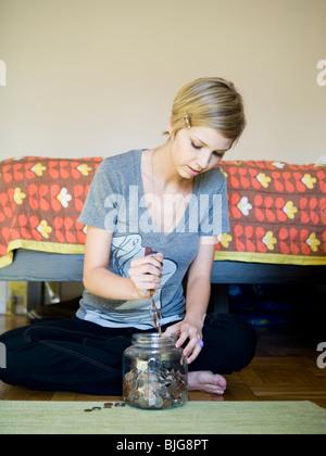 Frau, die Änderung in ein Glas setzen - Stockfoto