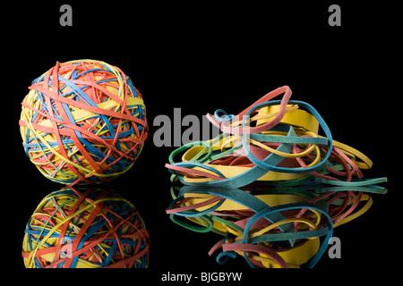 Gummiband-Ball neben einem Haufen von Gummibändern - Stockfoto