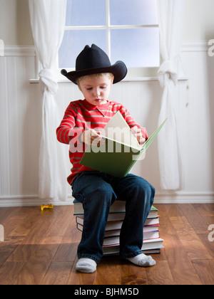 jungen tragen einen Cowboyhut, ein Buch zu lesen - Stockfoto