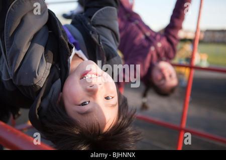 Jungen und Mädchen im Park schwingen auf barson Schule Spielplatz Spaß haben - Stockfoto