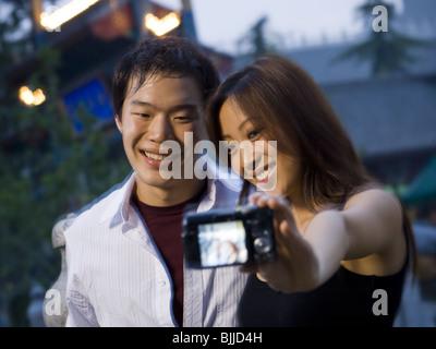 Paar umarmt und lächelnd im Freien mit Kamera - Stockfoto