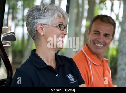 Älteres Paar in Golfwagen auf Golfplatz lächelndes - Stockfoto