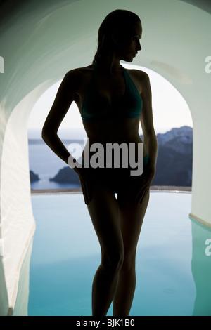 Silhouette der Frau im Badeanzug im Infinity-pool - Stockfoto