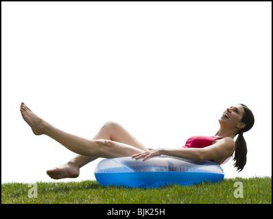 Frau im Bikini im Schwimmen Ring auf Rasen lächelnd liegend - Stockfoto