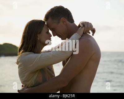 Mann und Frau umarmt im Freien am Strand - Stockfoto