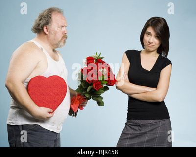 Zerzausten Mann mit Herz-Box und rote Rosen mit desinteressierten Frau - Stockfoto