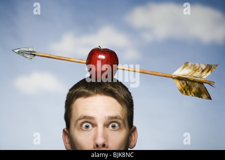 Mann im Freien mit Pfeil durch roter Apfel auf dem Kopf - Stockfoto