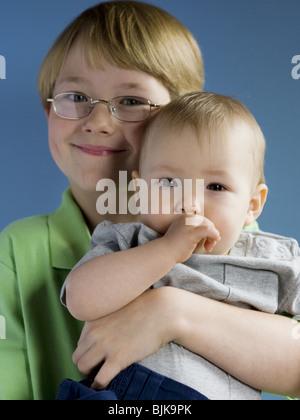 Junge mit Brille hält Baby mit den Augen bedeckt - Stockfoto