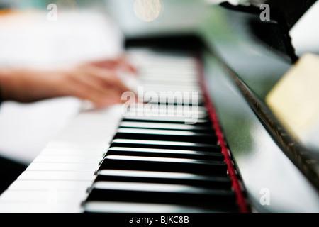 Hände auf einer Klaviertastatur Stockfoto