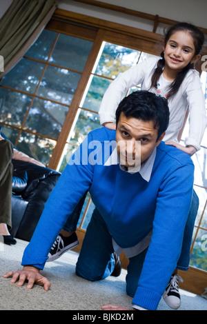 Mann mit Mädchen-Huckepack-Fahrt - Stockfoto