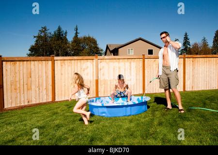 Mann mit Schlauch reden über Handy Spritzen junge mit Schlauch im Kinderbecken - Stockfoto