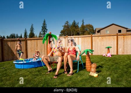 Familie im Hof mit Kinderbecken und cocktails - Stockfoto