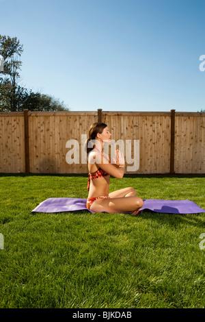 Frau beim Yoga im Hof mit blauem Himmel - Stockfoto
