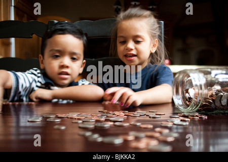 Junges Mädchen zählen Münzen aus Glas - Stockfoto