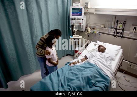 Eltern mit jungen im Krankenhausbett mit Kopf Bandagen - Stockfoto