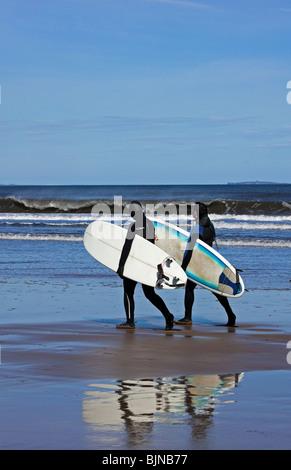 Zwei männliche Surfer zu Fuß in Richtung der Wellen an einem sonnigen Tag, Belhaven Bay beach, East Lothian, Schottland, - Stockfoto