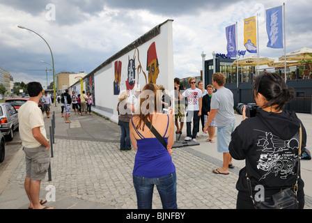 Eastside Gallery, junge Touristen an die lackierten, verbleibende Teil der Berliner Mauer im Bezirk Friedrichshain, - Stockfoto