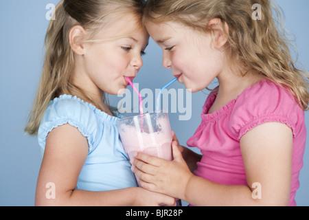 Zwei Mädchen teilen einen Milchshake - Stockfoto