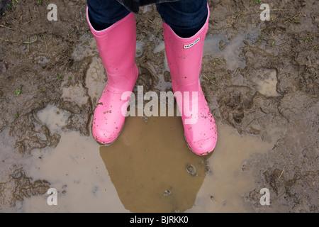 Ein paar helle Rosa Hunter Wellington (Gummistiefel) Stiefel Stand Schlamm bespritzt, imprägniert in einer Pfütze - Stockfoto