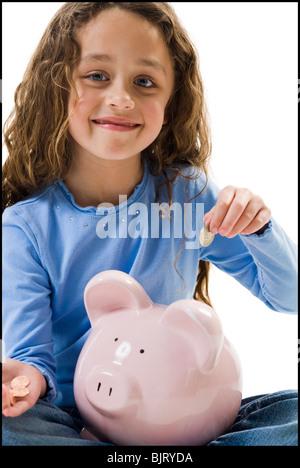 Junge Mädchen, die Hinterlegung von Geld im Sparschwein - Stockfoto