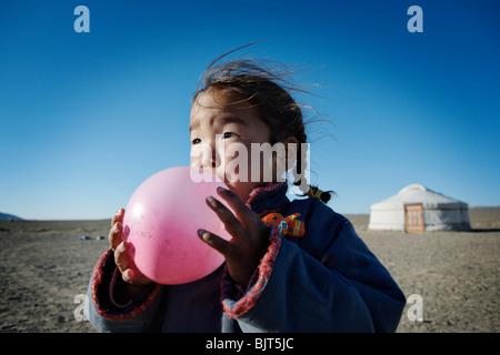 Mongolische Mädchen bläst einen Ballon in der Wüste Gobi, Mongolei. - Stockfoto
