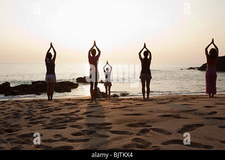 Frauen üben Yoga am Strand bei Sonnenuntergang - Stockfoto