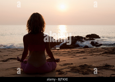 Frau praktizieren Yoga am Strand bei Sonnenuntergang - Stockfoto