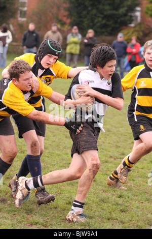 Junior jungen Rugbyspieler im Club Wettbewerb Spiel läuft mit dem Ball wird nur zur redaktionellen Nutzung in Angriff - Stockfoto