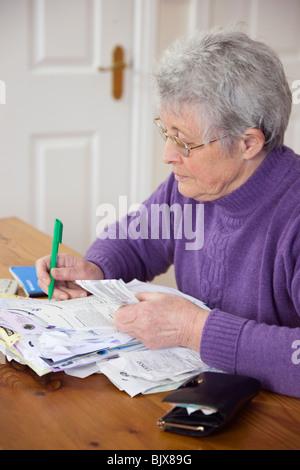 Ältere Frau Rentner OAP Dame zu Hause mit einer Vielzahl von Rechnungen auf dem Tisch die Kontrolle einer Kreditkarte Aussage gegen die Quittung. Großbritannien Großbritannien