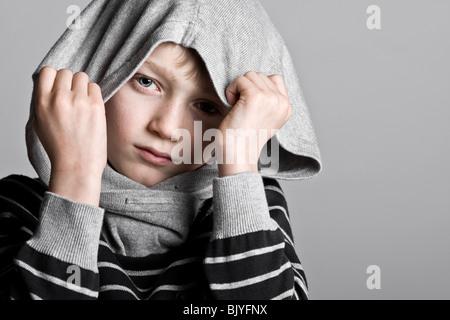 Schuss von eine junge Blonde junge versteckt sein Gesicht in Kapuzenshirt - Stockfoto