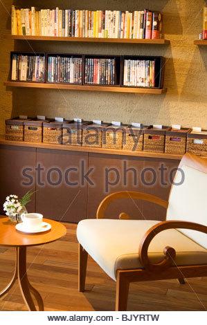 Stuhl und Tisch vor Regale mit Büchern, Dvds und CDs - Stockfoto
