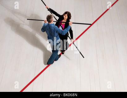 Mann und Frau balancieren auf schmalen Grat - Stockfoto