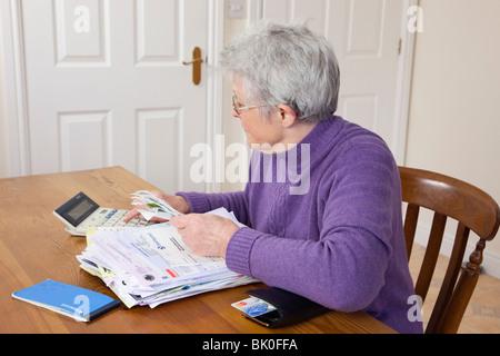 UK Senior Frau Rentner mit einem großen Haufen von Rechnungen auf dem Tisch, die Überprüfung der Belege für eine - Stockfoto
