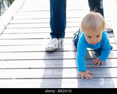 Baby Boy auf ein Dock mit seinem Vater - Stockfoto