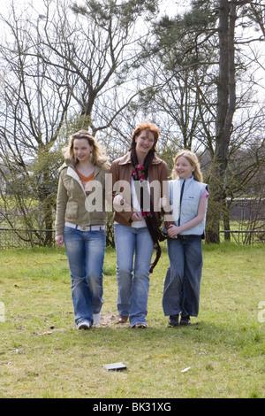 Mitte im Alter von Mama zu Fuß mit ihren beiden Kindern draußen im park - Stockfoto