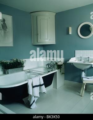 Roll-Top Badewanne und weiße Wand-Eckschrank in grau-blau ...