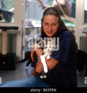 Teenager-Mädchen freiwillige Arbeitskraft im Tierheim eine Tabby Katze in ihre Arme und glücklich Blick in die Kamera - Stockfoto