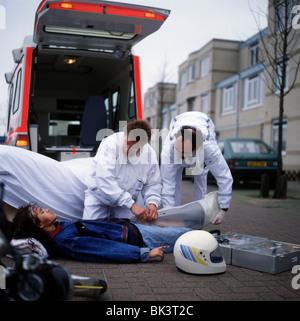 Notarzt und Sanitäter kümmert sich Teenager-Mädchen nach Unfall - Stockfoto